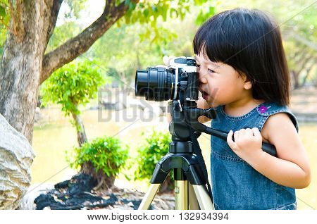 Two years old little girl taking photograph using single lens reflex camera on tripod outdoor in a park. Kid have fun practicing photography.