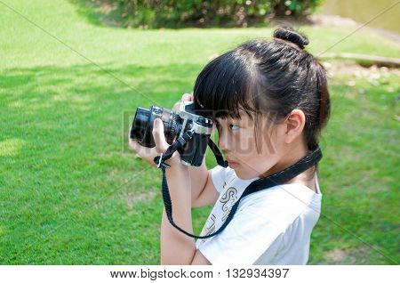 Seven years old girl taking photograph using single lens reflex camera on tripod outdoor in a park. Kid have fun practicing photography.
