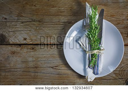 Rustic place setting plate with silverware napkin and rosemary bunch on an old wooden table plenty of copy space in the background view from above