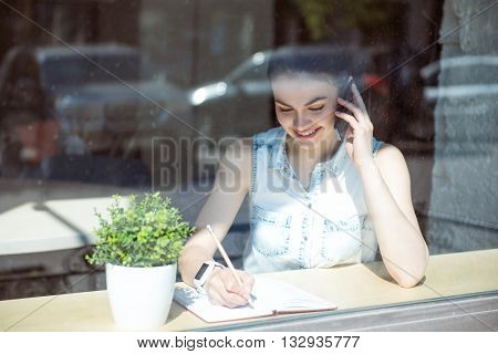Working moments. Happy and smiling modern young woman talking on a smartphone and sitting near a window in a cafe while writing something in her copybook