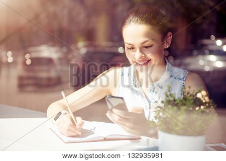 Important  details. Smiling and cheerful modern young woman typing text messages using her cell phone while sitting near a window in a cafe and writing something in her copybook