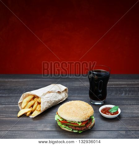 Fast food. Hamburger, potato wedges, cola drink. Takeaway food. Wrapped French fries, Cola glass, tomato sauce, double cheese hamburger at rustic wood and red background.