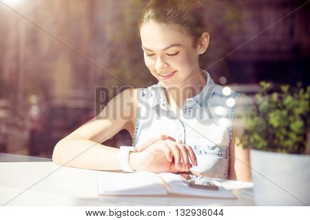 Modern  time. Positive and merry modern young woman checking time on her smart watch and typing text messages using her cell phone while sitting near a window in a cafe and writing something in her copybook