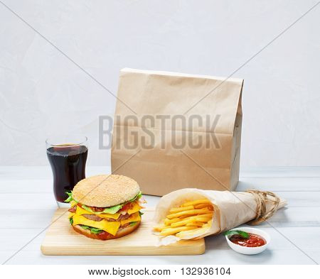 Fast food. Brown paper package with copyspace. Hamburger, potato fries, cola drink. Takeaway food. Wrapped French fries, paper bag, Cola glass, tomato sauce, double cheeseburger at wood.