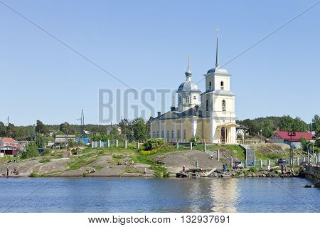 PETROZAVODSK, RUSSIA - MAY 29TH, 2016: Christian orthodox church on the shore of Lake Onega on a rock a clear summer day, the locals catching fish near the church in Petrozavodsk, Republic of Karelia, Northern Russia
