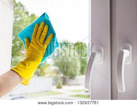 woman washing the window with a cloth hand closeup