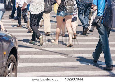 a lot of pedestrians walk on a crosswalk on sunny summer day