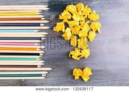 Creative idea concept with crumpled paper lightbulb and row of colorful pencils on dark wooden desktop