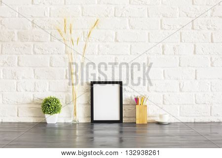 Blank picture frame pencil holder plant wheat spikes and coffee cup on wooden desktop and white brick wall background. Mock