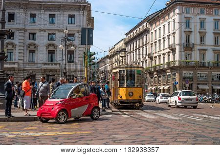 Milan Italy - May 25 2016: Crossroads in Piazza della Scala. Yellow tram and red car.