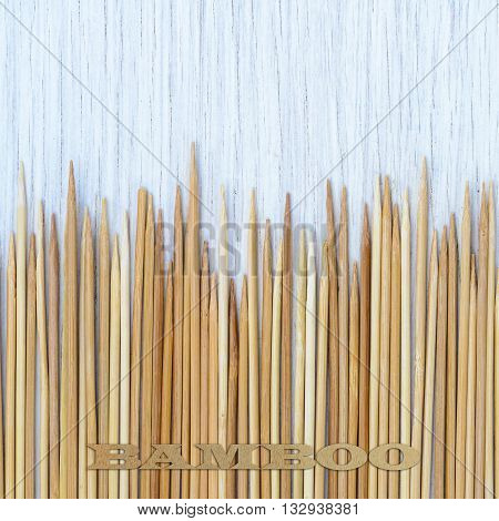bamboo sticks on white wooden background. With logo bamboo.