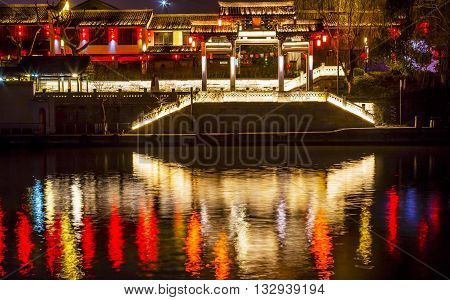 Chinese Gate Grand Canal Buildings Lights NIght Reflection Hangzhou Reflection Zhejiang China. Created 500s AD the oldest and longest canal from Hangzzhou to China over 1000 miles. Symbol on bridge is a generic symbol of Buddhism.