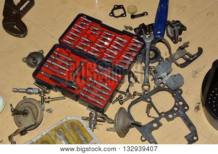 Truck carburetor in need of cleaning and rebuild.  A mechanic is in the process of rebuilding using necessary tools and repair kit.
