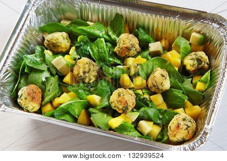 Healthy eating, diet concept. Creative healthy food. Healthy vegetarian lunch, Take away organic food. Weight loss diet, food take away in aluminium box. Falafel with mango cubes and spinach, closeup