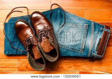Jeans with brown leather boots over wooden floor