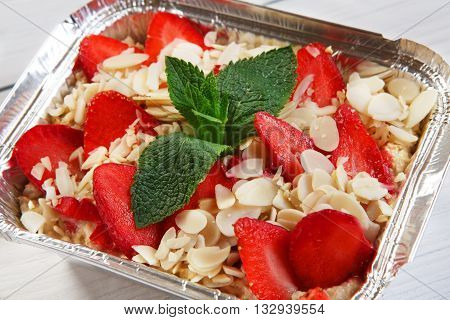 Healthy eating, diet concept. Healthy lunch, dessert. Take away organic food. Weight loss diet, take away in aluminium box. Healthy food. Oatmeal porridge with strawberries and almond slices closeup