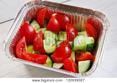 Healthy eating, diet concept. Healthy lunch, Take away organic food. Weight loss diet, food take away in aluminium box. Vegetable salad from tomatoes and cucumbers at white wood, closeup