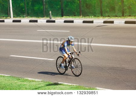 Cycling training on the summer road. Sport bicycle. Woman cycling on countryside summer road or highway. Training for triathlon or cycling competition. Highway cycling