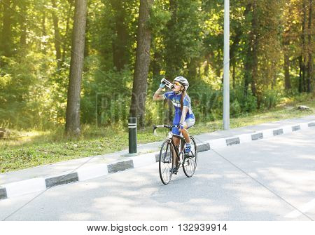 Female sportsman cyclist drinks water from the bottle while cycling the race. Cycling at the road. Triathlon or cycling competition. Thirsty cyclist, rest at race or training.