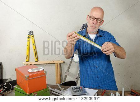 a portrait of mature handyman at DIY workshop