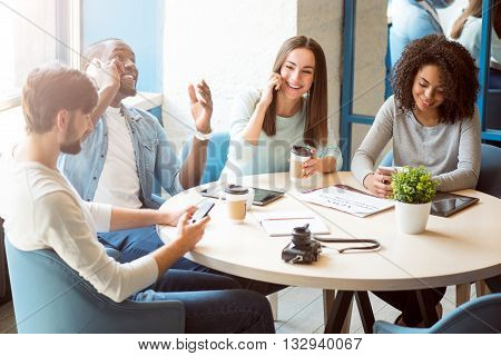 Sharing moment. Smiling and cheerful group of modern young people sitting in a cafe and drinking coffee while talking on their mobile phones and typing messages