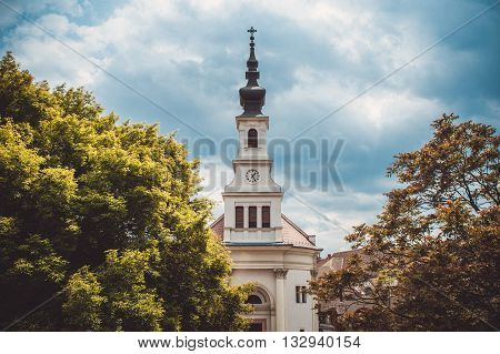 The spire of the Lutheran Church with the clock on the castle hill in Budapest against the sky. Vintage photo spring-fall