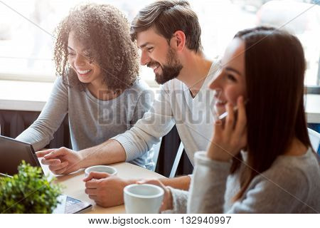 Cheerful lifestyle. Smiling and positive group of young people sitting together, drinking coffee while using a laptop and a smartphone