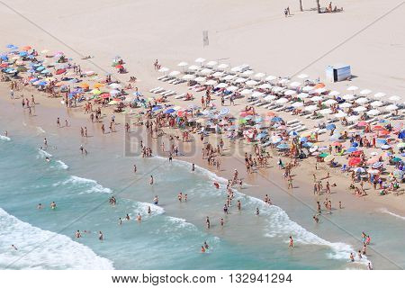 Aerial view of beach ocean waves and people walking on sand on Spain beach