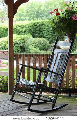 shiny black rocking chair on outdoor gazebo