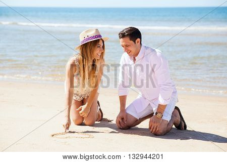 Couple Drawing Initials On The Sand