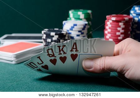 Casino chips and royal flush cards combination on the green table.