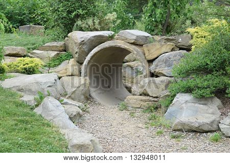 a dirt path leads to a stone covered tunnel.