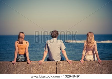 Happiness summer friendship concept. Group of friends spending time together having fun outdoor looking on sea horizon back view