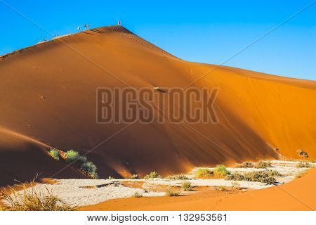 Travel to Namibia. Namib-Naukluft National Park. Tourists and photographers climb the sharp ridge of high dunes