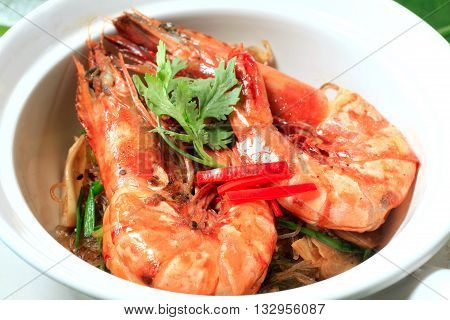 Shrimp and vermicelli baked together with a special sauce on white plate stock photo.