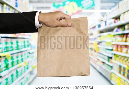 Businessman hand holding brown paper bag, with defocus aisle background