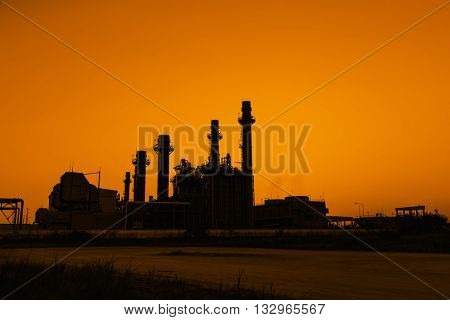 Silhouette gas turbine electrical power plant at dusk