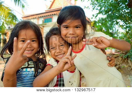Tonle Sap Lake, Siem Reap Province, Cambodia - November 19, 2014:   The young girls belonged to a floating village community on the Tonle Sap Lake.  The community buildings are a meeting place for the villagers and are located on land (terra firma). There