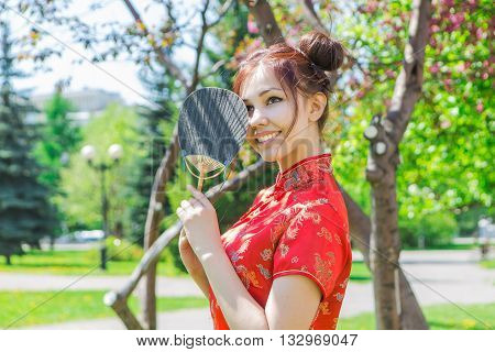 Beautiful Asian Girl In Traditional Chinese Red Dress With Bamboo Fan.