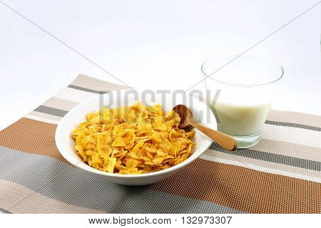 Bowl of cornflakes with a cup of milk on colorful table mat