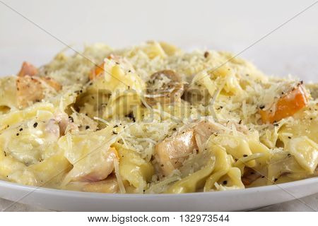 Tortellini and Ravioli with sour cream chicken meat and mushrooms on plate