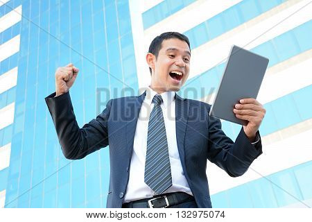 Businessman raising his fist while looking at tablet pc - success winning & overcome concepts