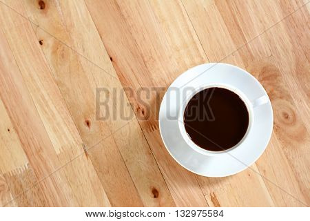 Coffee cup on wood table, top view