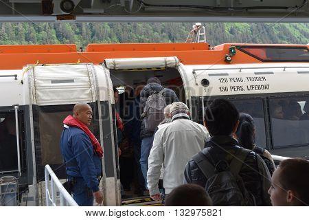 JUNEAU, ALASKA, USA.  MAY 18, 2016.  Cruise ship passengers board a tender for a shore excursion.