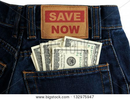 US dollars of value 100 in Blue Denim Jeans Pocket and message Save Now symbolize Concept of saving money