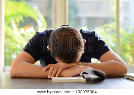 Young Man Sleeping On The Table With Book Opened, Weary & Tired Of Reading (studying)