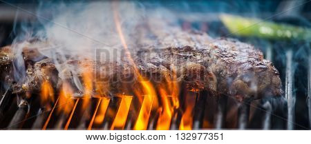 Delicious steak on the grill with fire, close up