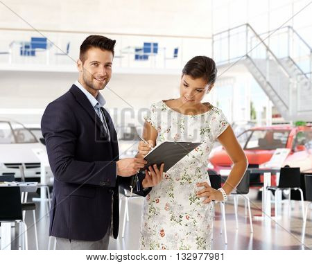 Young casual caucasian woman signing business contract with pen at car dealership saloon indoors. Smiling, standing salesman holding clipboard with documents, looking at camera.
