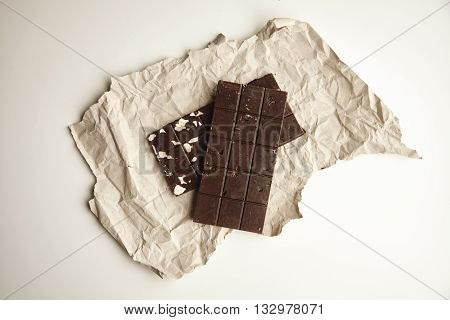 Top View On Two Different Rustic Chocolate Bars Freshly Baked , On Craft Paper, Isolated On White Ta