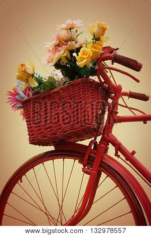 Detail of a red painted bicycle with basket full of flowers against a yellow background